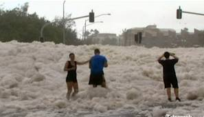 People playing in the foam from the ocean